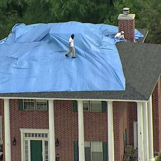 tarping a roof with storm damage
